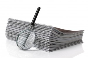 Stack of binders with magnifying glass