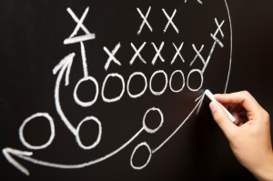 Designing football play on chalkboard